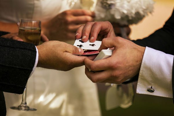 Magician doing card magic for bride and groom